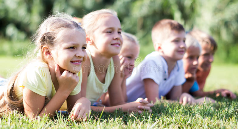 Group of positive kids lying on green grass in park royalty free stock photography