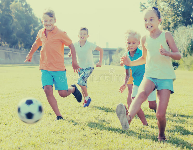 Group of positive kids playing football together on green lawn i stock photography
