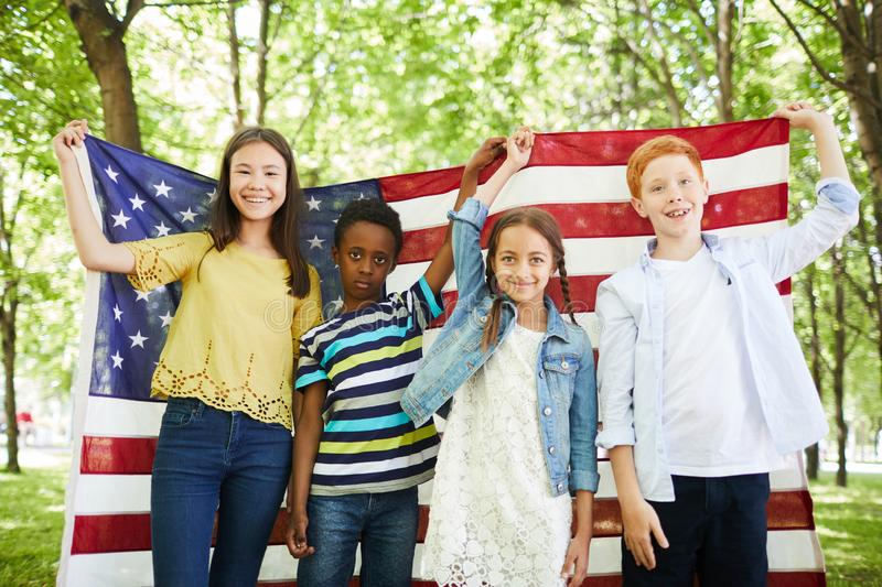 Positive multi-ethnic kids holding American flag royalty free stock images