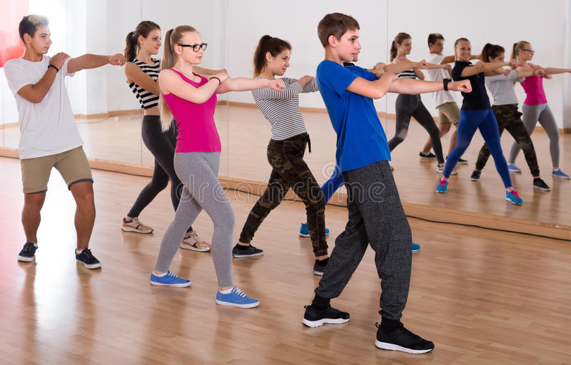 Group of positive smiling teenagers dancing in classroom royalty free stock image