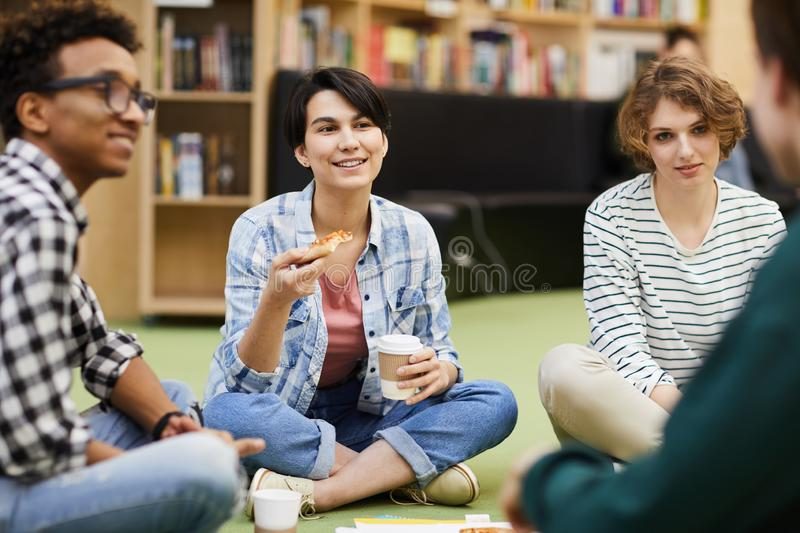 Positive students having lunch break in library stock photos