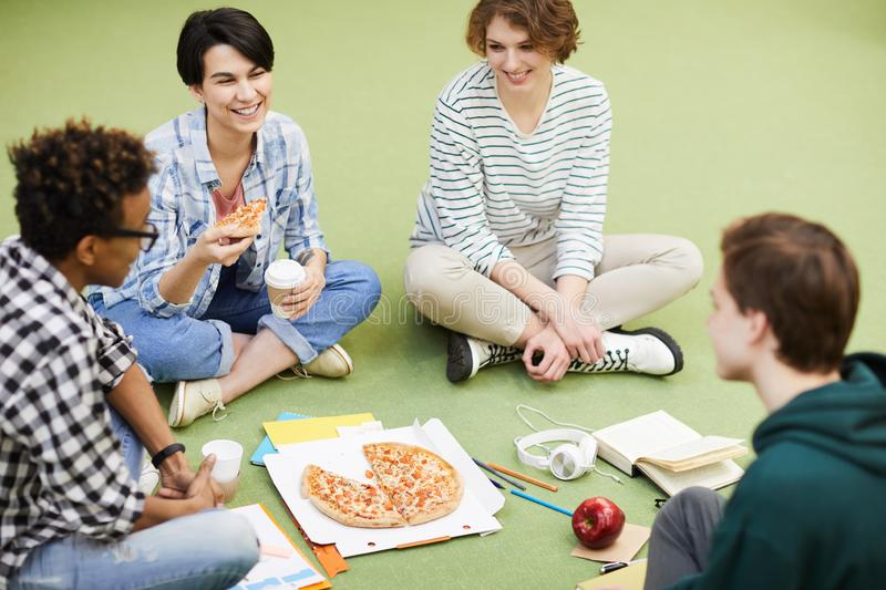 Students eating pizza stock photography