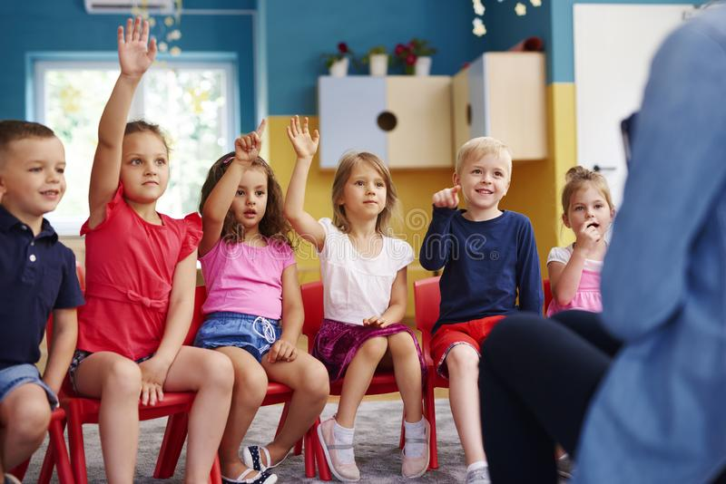 Group of preschool children answering a question. In the preschool stock image
