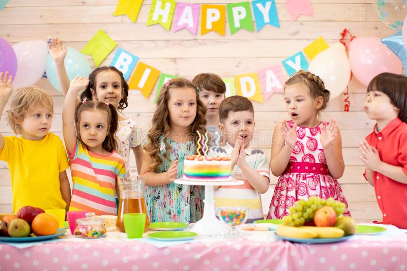 Group of preschool kids gathered around birthday cake with candles stock image