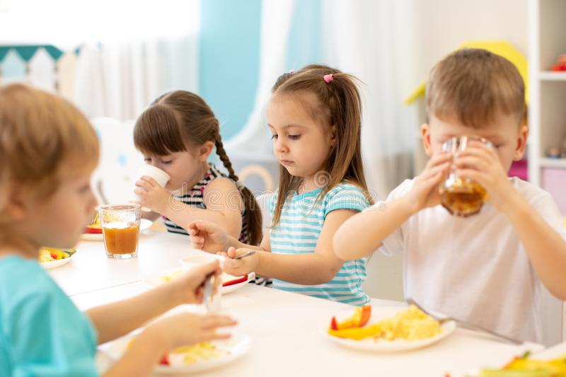 Group of preschool children have a lunch in daycare. Kids eating healthy food in kindergarten. Group of preschool children have a lunch in day care. Kids eating royalty free stock photography