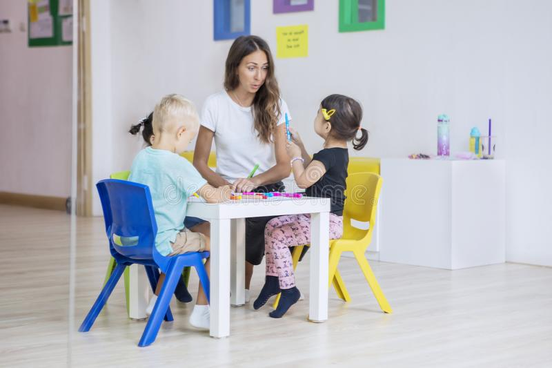 Preschool kids draw on the table with their teacher. Group of preschool kids drawing on the table with their teacher in the kindergarten royalty free stock photo