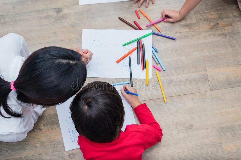 Group of preschool student and teacher drawing on paper in art c stock photography