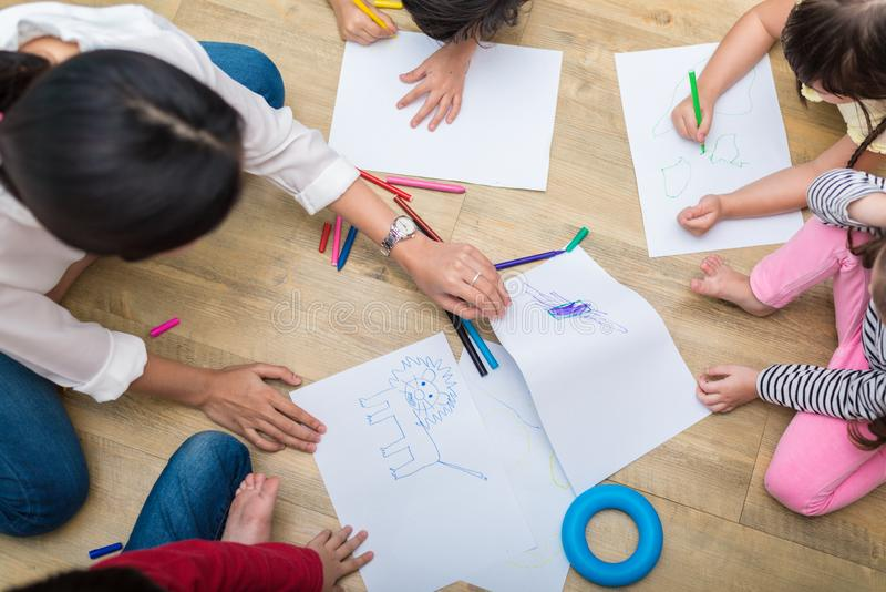 Group of preschool student and teacher drawing on paper in art c. Lass. Back to school and Education concept. People and lifestyles theme. classroom in nursery royalty free stock images