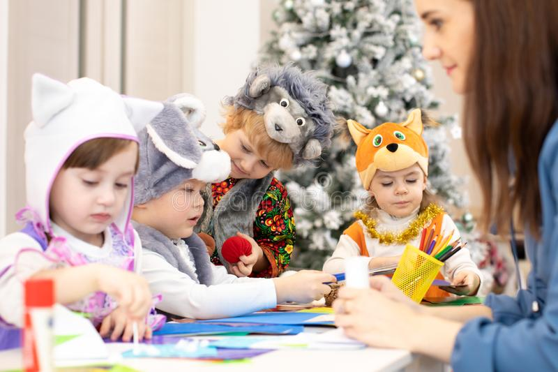Group of preschoolers weared funny clothes on lesson in classroom. Kids with teacher make hands crafts in kindergarten royalty free stock photos
