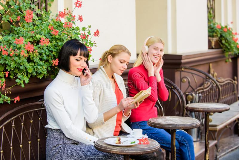 Group pretty women cafe terrace entertain themselves with reading speaking and listening. Information source. Female stock image