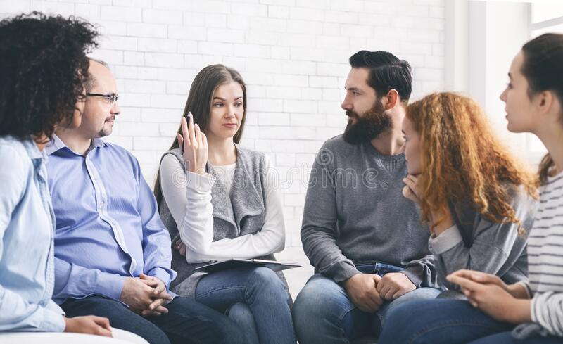 Group of problematic people listening to psychotherapist stock images