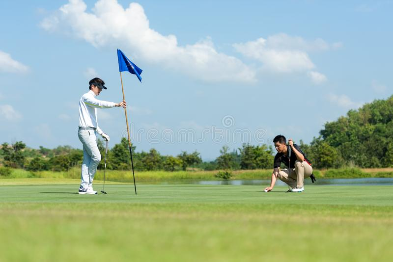Group Professional Golfer asian man and friend playing aiming shot for putting ball on the hole with club on green course.  Hobby. Group Professional Golfer stock photography