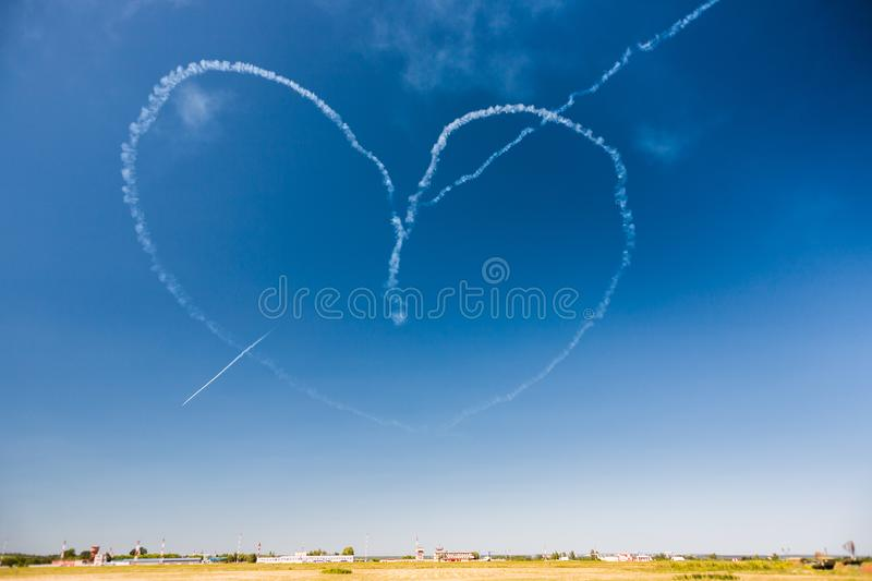 A group of professional pilots of aircraft of fighters on a sunny clear day shows tricks in the blue sky, drawing a romantic heart stock photo