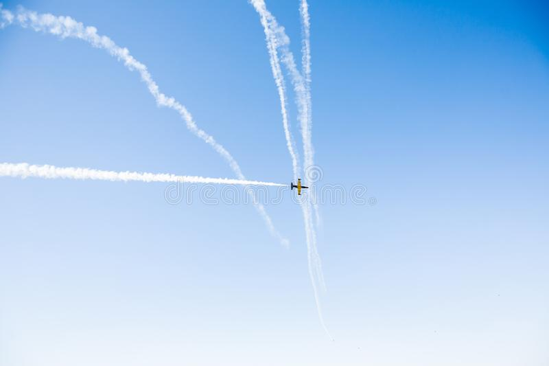 A group of professional pilots of military aircraft of fighters on a sunny clear day shows tricks in the blue sky stock images