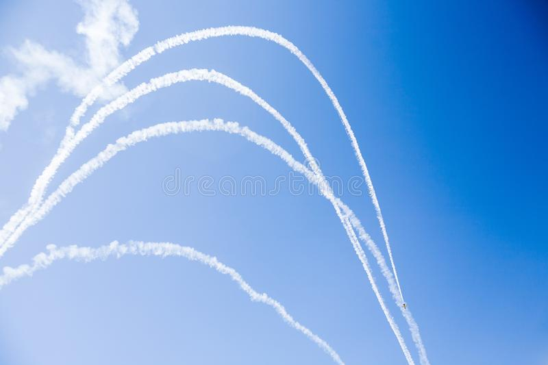 A group of professional pilots of military aircraft of fighters on a sunny clear day shows tricks in the blue sky, leaving beauti. Ful traces of clouds scattered stock photos