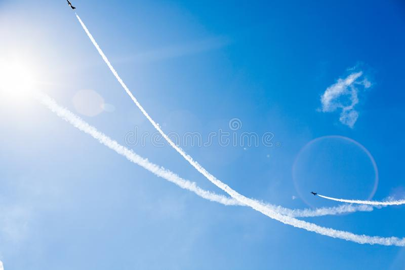 A group of professional pilots of military aircraft of fighters on a sunny clear day shows tricks in the blue sky, leaving beauti royalty free stock photos