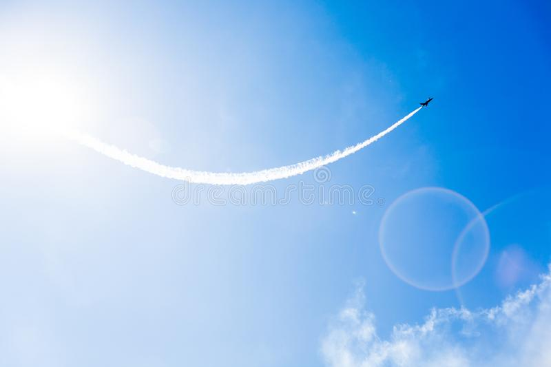 A group of professional pilots of military aircraft of fighters on a sunny clear day shows tricks in the blue sky stock image
