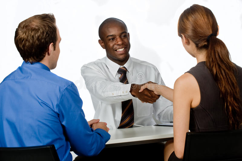 Group of Professionals. A young and professional businessman shaking hands and securing a deal in his office stock photography