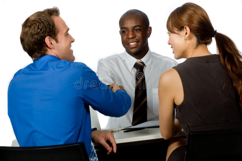 Group of Professionals. A young and professional businessman shaking hands and securing a deal in his office stock images