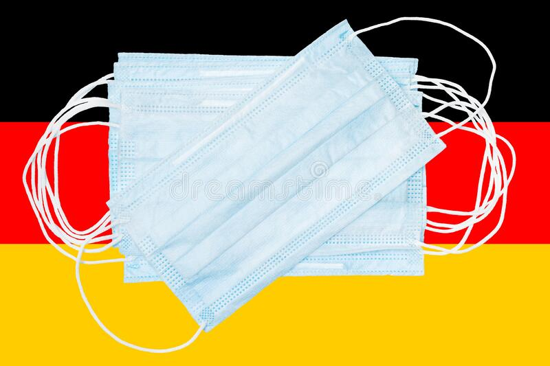 Group protective medical surgical face masks on background colors flag of German or Germany national flag royalty free stock photo