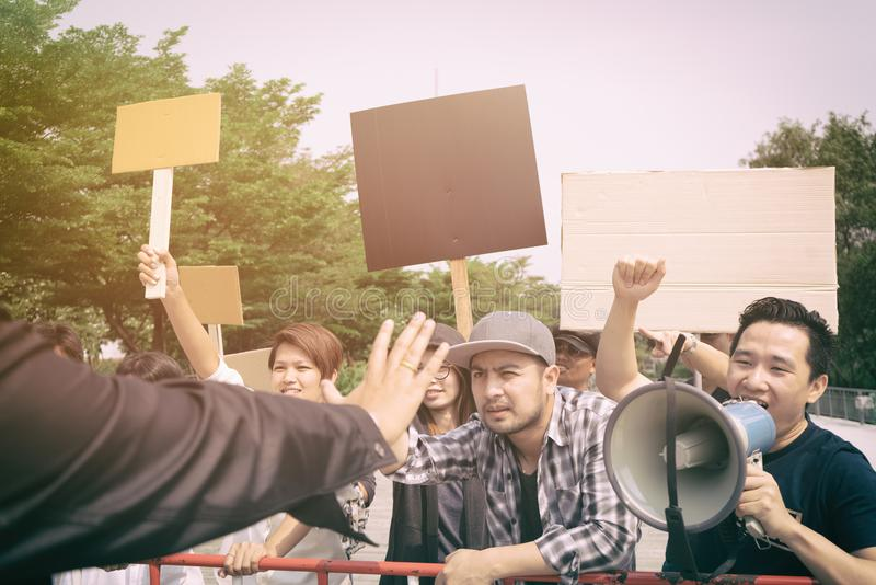 Group of protesters walking at the street. Group of protesters holding protest signs walking at the street stock photos