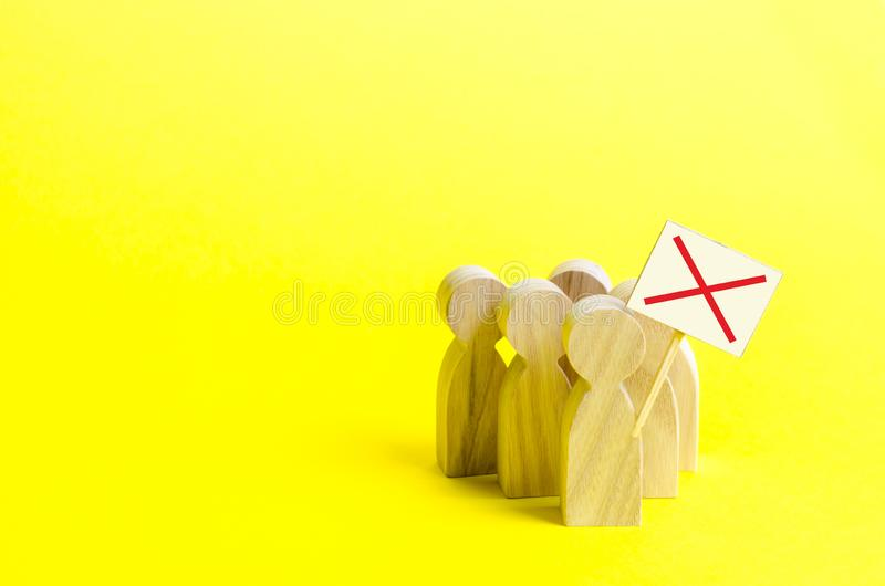 A group of protesting figures with signs on an yellow background. An angry mob of wooden figures of people with a poster. stock photography
