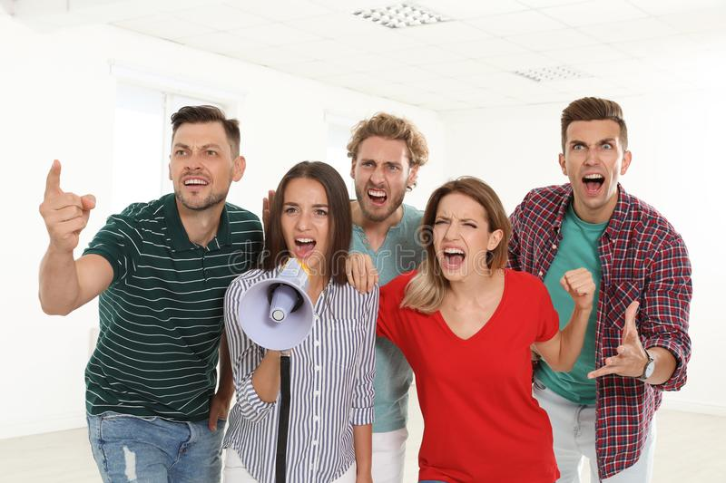 Group of protesting young people. With megaphone indoors stock photography