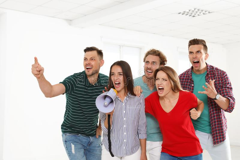Group of protesting young people with megaphone. Indoors stock photo