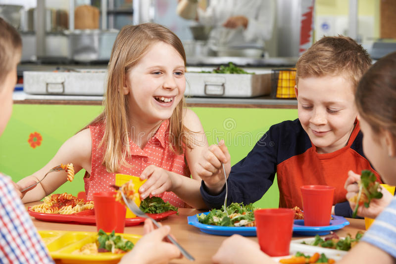 Group Of Pupils Sitting At Table In School Cafeteria Eating Lunch royalty free stock photography