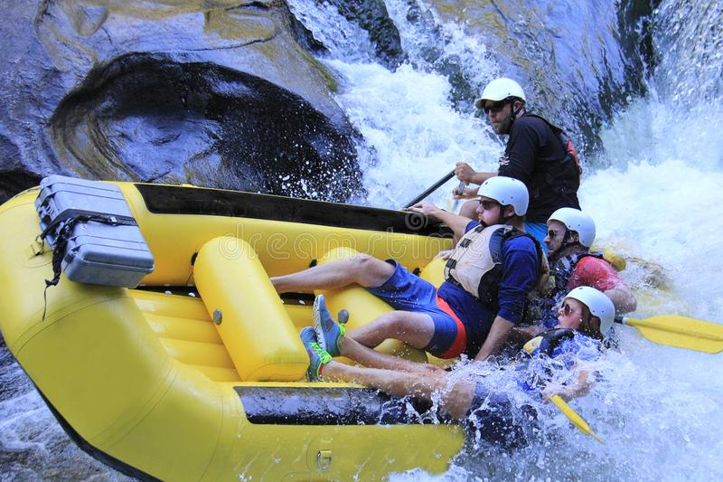 A group rafting down raging rapids stock images