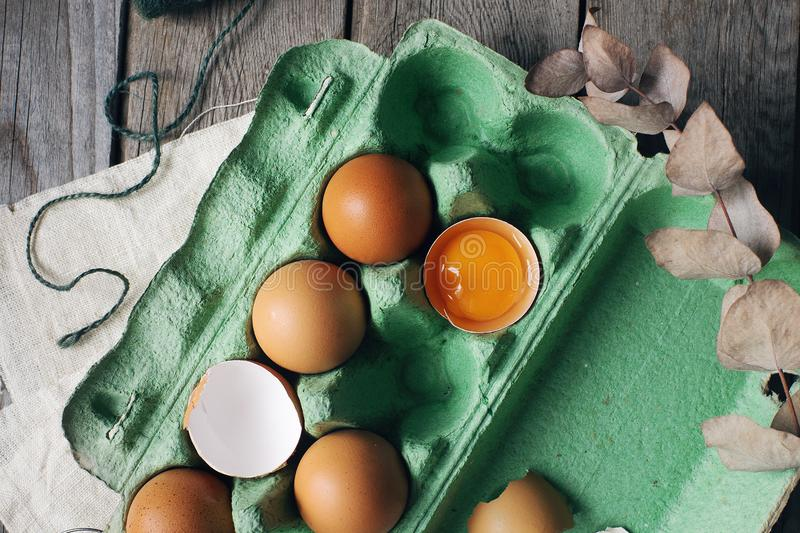 Group of raw brown chicken eggs in green paper tray on rustic wooden table, fresh half cracked egg stock images