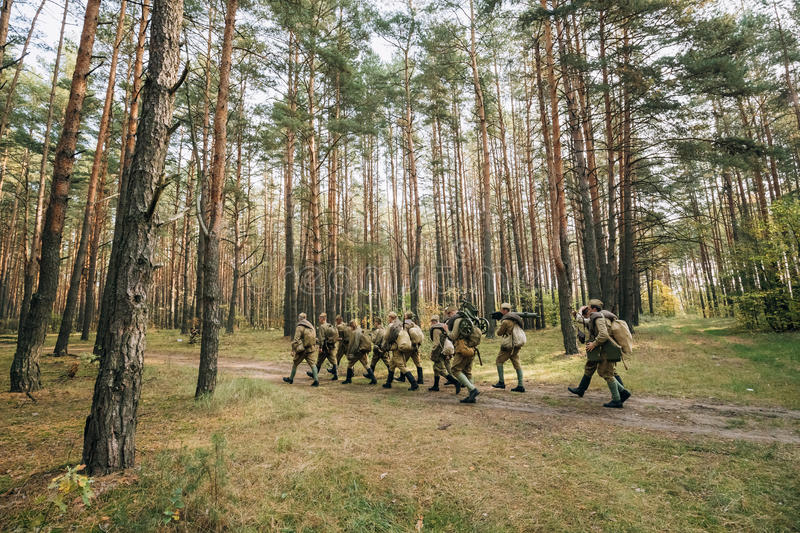 Group Of Re-enactors Dressed As Soviet Russian Red Army Infantry. Soldiers Of World War II Marching Along Forest Road At Summer Autumn Season royalty free stock photography