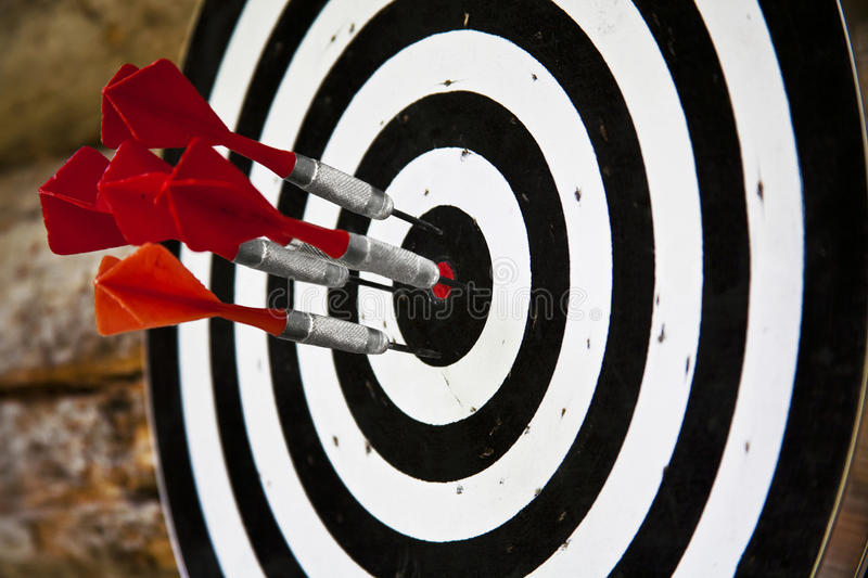 Group of red darts. Red darts on black and white dartboard royalty free stock image
