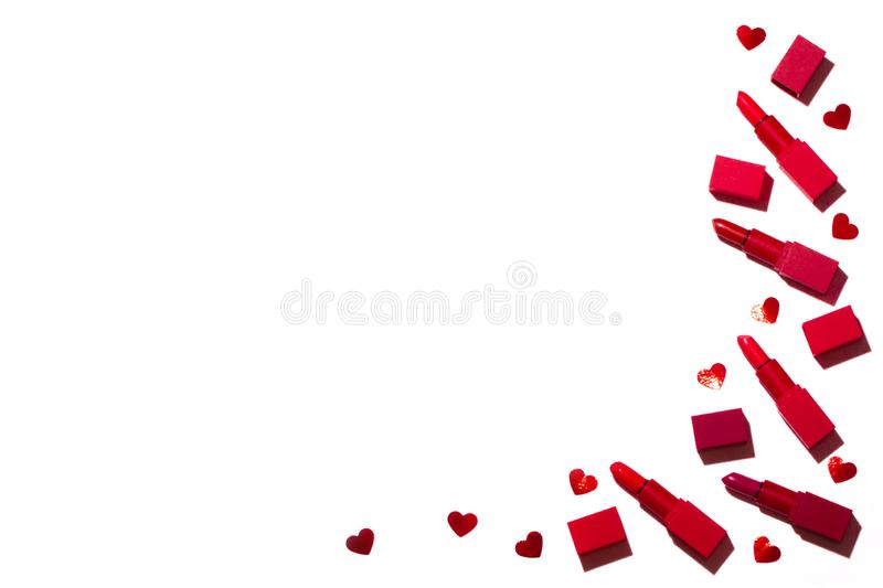 Group of red lipsticks spread with confetti in the form of hearts on a white background. stock photos