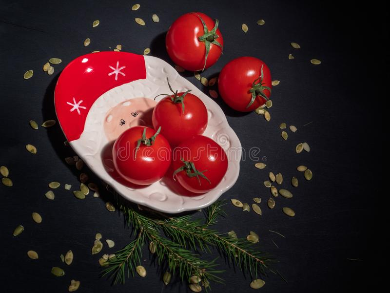 A group of red tomatoes on a New Year`s plate on a dark background around pumpkin seeds stock images