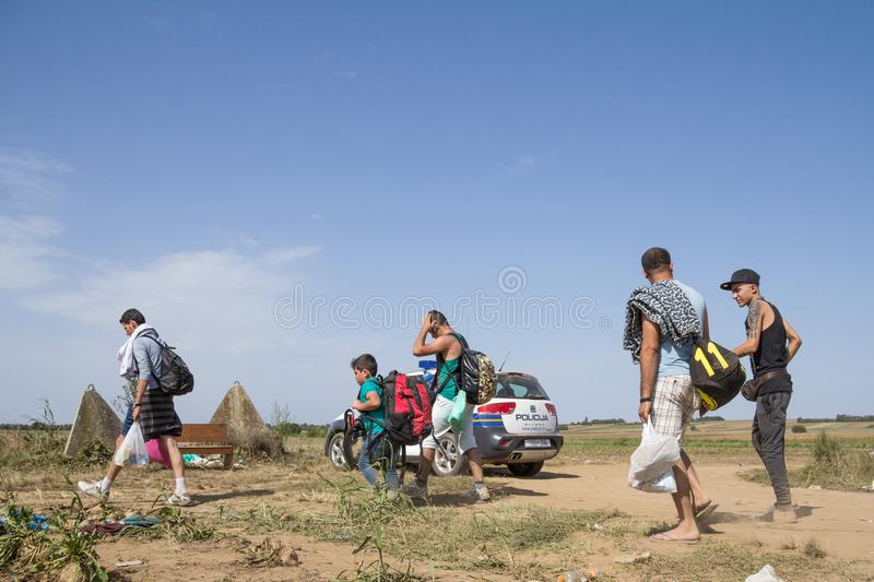 Group of refugees, from passing in front of a Croatian police car while crossing the Serbia Croatia border in Tovarnik Sid. TOVARNIK, CROATIA - SEPTEMBER 19 royalty free stock photos