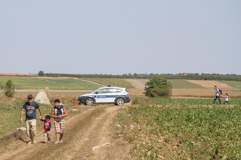 Group of refugees, from passing in front of a Croatian police car while crossing the Serbia Croatia border in Tovarnik Sid. TOVARNIK, CROATIA - SEPTEMBER 19 royalty free stock image