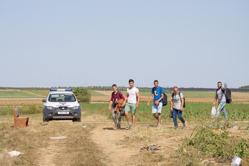 Group of refugees, from passing in front of a Croatian police car while crossing the Serbia Croatia border in Tovarnik Sid. TOVARNIK, CROATIA - SEPTEMBER 19 royalty free stock photo