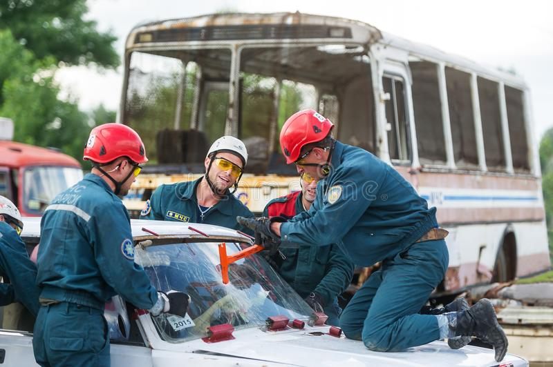 Group of rescuers pull out the victim from the broken car after road accident royalty free stock photo