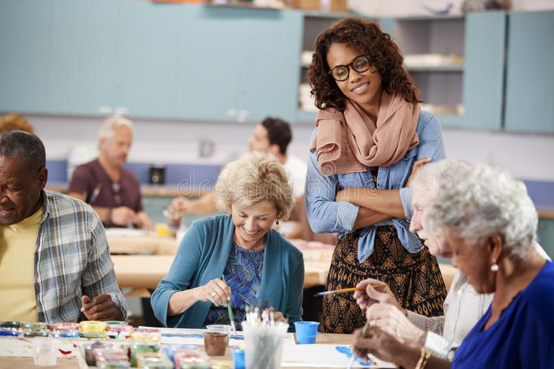Group Of Retired Seniors Attending Art Class In Community Centre With Teacher royalty free stock photo