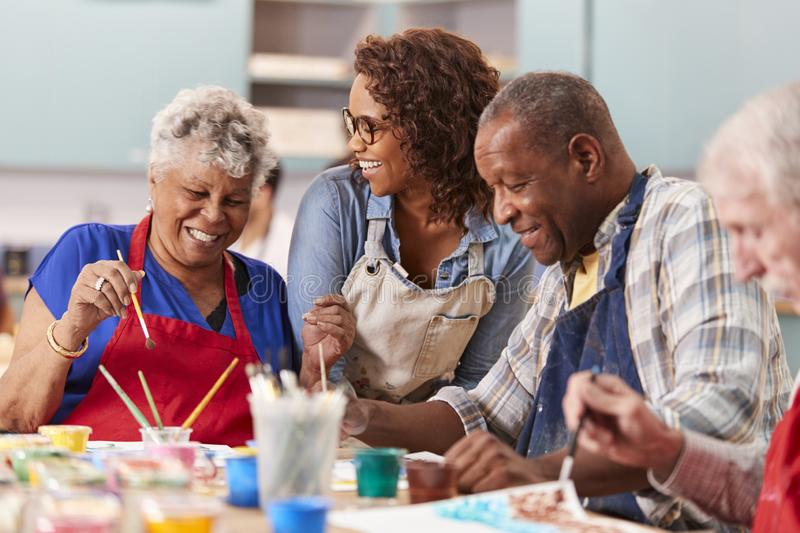 Group Of Retired Seniors Attending Art Class In Community Centre With Teacher stock photos