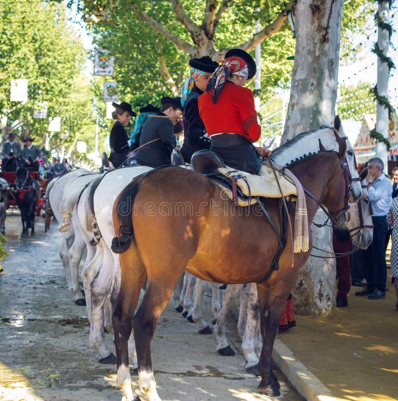 Group of riders on horseback enjoy April Fair, Seville Fair Feria de Sevilla. Seville, Spain - April 18, 2018: Group of riders on horseback enjoy April Fair royalty free stock photography
