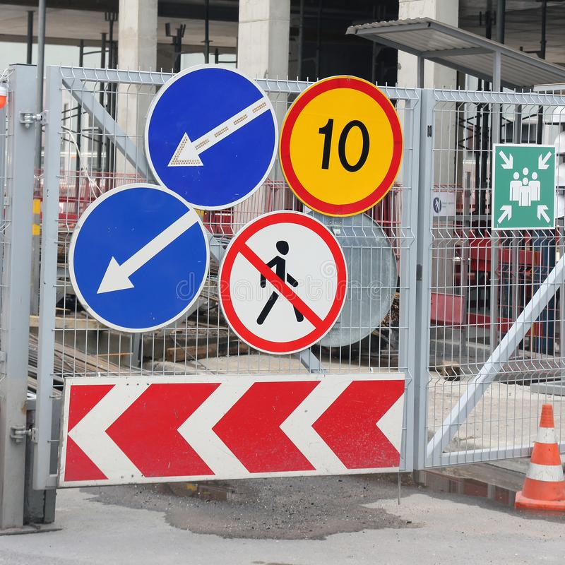 Group of road traffic signs on the metal gate of the construction site. Closeup royalty free stock photos