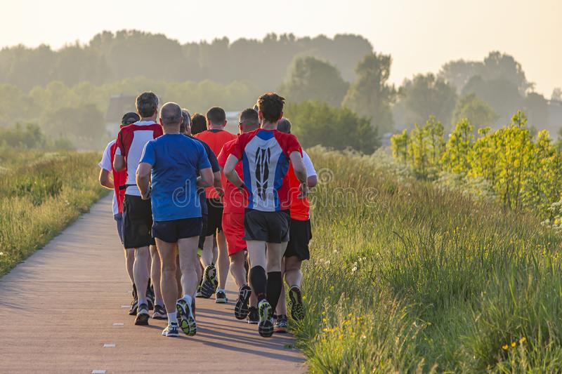A group of runners enjoy the evening sun on the footpath along lake Noordhovense Plas in Zoetermeer, Netherlands.  stock photo