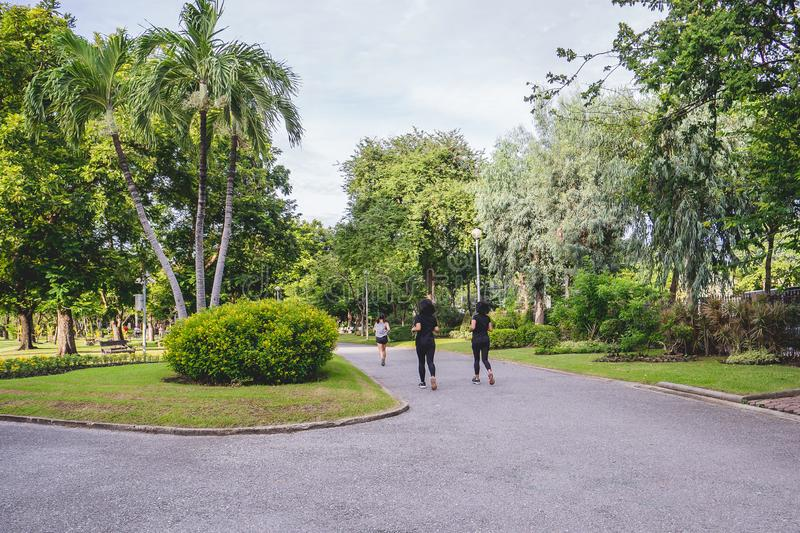 Group Of Runners Jogging Through Park, exercising in the morning at city park stock photos