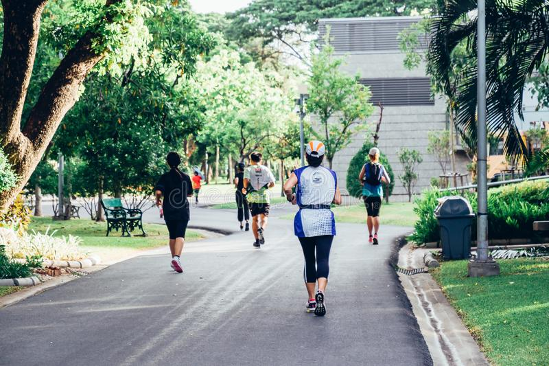Group Of Runners Jogging Through Park, exercising in the morning at city park royalty free stock images