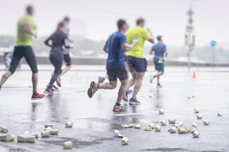 Group of runners on marathon at service point. Pile of used disposable white cardboard cups for beverages, selectiv stock image