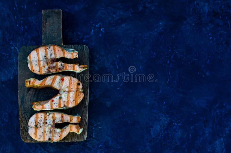 Group salmon steaks pepper salt top view on the cutting board on the dark background space. Group salmon steaks pepper salt top view on dark background stock image