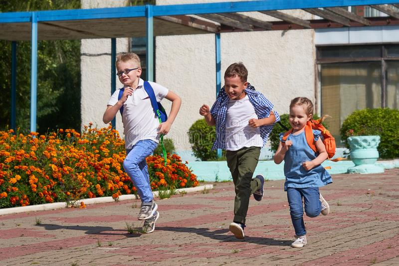 A group of school children running out of school. A group of students runs out of school happy and happy. boys and girls have completed primary school. go back royalty free stock photo