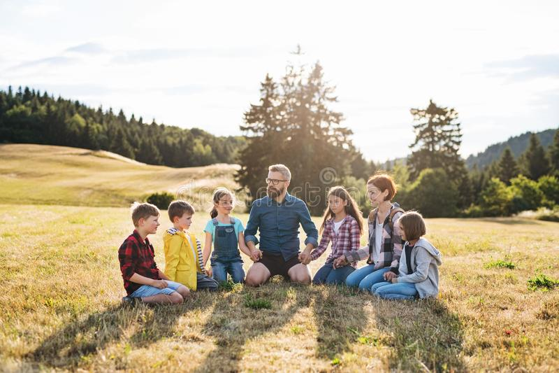 Group of school children with teacher on field trip in nature, holding hands. stock photos
